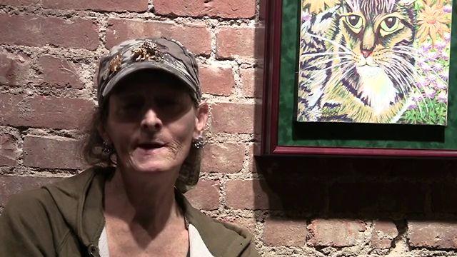 Siobhan Meow posando con uno de sus cuadros