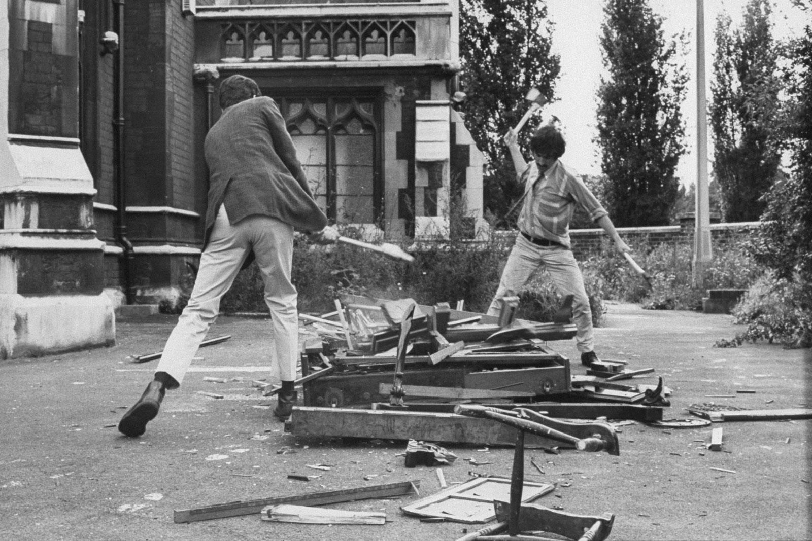 Rafael Ortiz (izquierda) y Paul Pierrot destruyendo un piano durante el Simposio de destrucción en el Arte